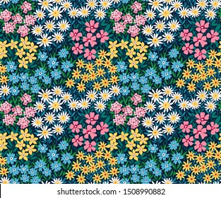 Vintage floral background. Seamless vector pattern for design and fashion prints. Flowers pattern with small colorful flowers on a dark blue background. Ditsy style.