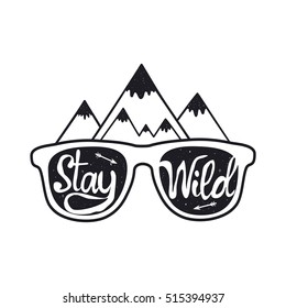 Vintage hipster vector illustration. Hand drawn style typography poster with sunglasses, mountains, arrows and quote. Stay Wild. T-shirt print, inspirational and motivational design