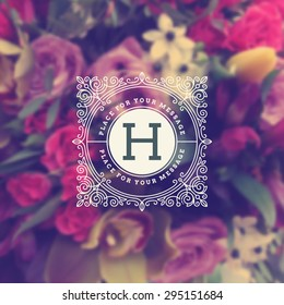 Vintage monogram logo template with flourishes elegant ornament elements on a blurred flowers background. Design with letter for cafe, shop, store, restaurant, boutique, hotel, fashion and etc.