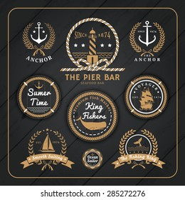 Vintage nautical anchor labels logo with rope and laurel wreath design on dark wood background.