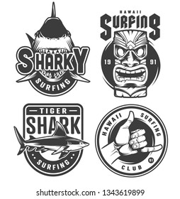 Vintage surfing monochrome emblems with sharks hawaiian tiki mask and surfer shaka hand sign isolated vector illustration