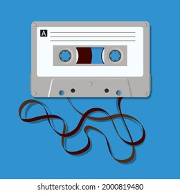 Vintage symbol of the 70s, with an audio cassette from which the magnetic tape is unwound