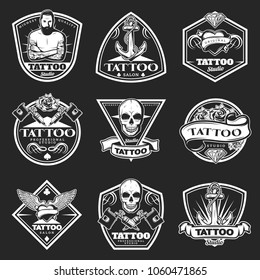 Vintage tatoo studio logos set with master machine wings skull ribbons flowers heart diamond anchor on dark background isolated vector illustration