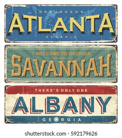 Vintage tin sign collection with US cities. Atlanta. Savannah. Albany. Retro souvenirs or old postcard templates on rust background.