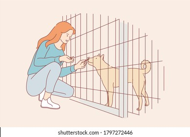 Volunteering, care, love, affection concept. Young happy smiling woman girl volunteer cartoon character feeding food dog pet friend in nursery. Adoption stray animal from special shelter illustration.