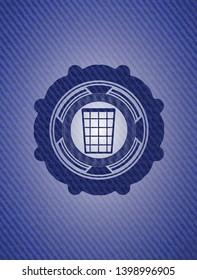 wastepaper basket icon inside emblem with jean background
