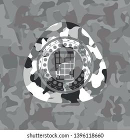 wastepaper basket icon inside grey camouflaged emblem