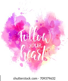 "Watercolor imitation heart shaped pink background with ""Follow your heart"" handwritten modern calligraphy message. Vector illustration"