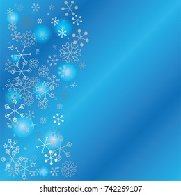 Wavy Christmas background with random scatter falling silver snowflakes, blue blurred lights and sparkles on a blue background