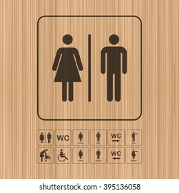 WC - Toilet door/wall plate. Original WC icons set on wooden background. The washroom signs set.