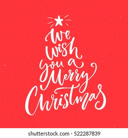 We wish you a Merry Christmas text. Calligraphy text for greeting cards on red background.