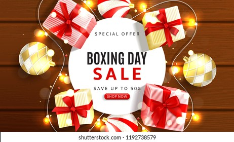 Web banner for Boxing day sale. Top view on realistic gift boxes, garlands and Christmas balls on rustic wooden texture. Vector illustration with confetti and effect bokeh.
