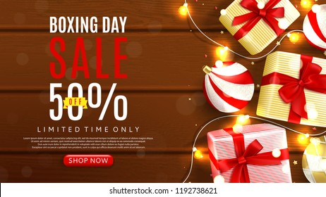 Web banner template for Boxing day sale. Top view on realistic gift boxes and Christmas balls on rustic wooden texture. Vector illustration with confetti and effect bokeh.