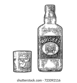 Whiskey glass with ice cubes and bottle label with barrel. Vector black engraving vintage illustration isolated on white background. Hand drawn design element.