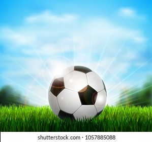 White and black soccer ball on the green glade with grass. Background with blue sky, sunshine and sport equipment for playing football.