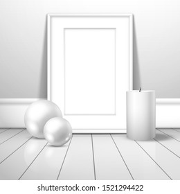 A white blank frame for a picture or poster and two white balls and a wax candle stands near the wall on the boards. Mockup for gallery design with shadow