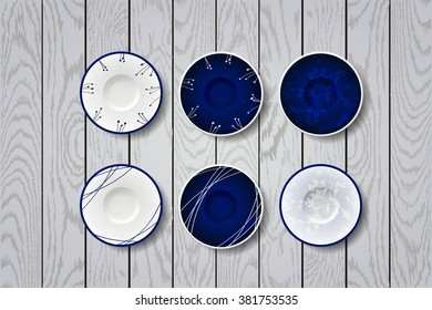 white and blue plate on  wooden white background. dishes with flowers ornament