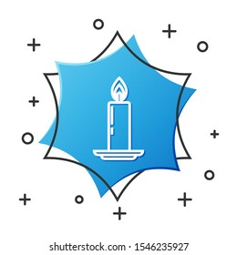 White line Burning candle in candlestick icon isolated on white background. Old fashioned lit candle. Cylindrical candle stick with burning flame. Blue hexagon button. Vector Illustration