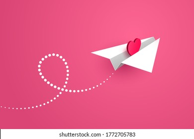 White paper airplane with red heart symbol inside is flying forward over pink background, white contrail is behind. Concept of love message, Valentine's day greetings, declaration of love
