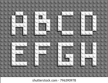 White plastic letters from building lego bricks. Gray lego background