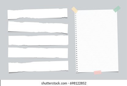 White ripped note, copybook, notebook paper strips stuck with sticky tape on grey background.