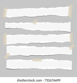 White ripped paper strips for note or text stuck with sticky tape on gray background.