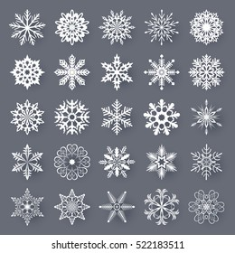 White snowflake shapes set isolated on grey background. Vector collection of snow flakes silhouettes.