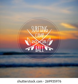 White vector surfing camp logo on blurred ocean sunset photo background