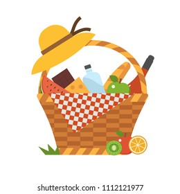 Wicker picnic basket with wine and french bread. Opened food hamper with blanket for romantic picnic.