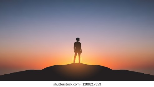 widescreen Silhouette of man standing on top of Mountain cliff looking at sunrise background