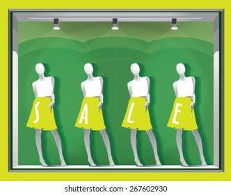 window display with mannequins and text SALE on a green background