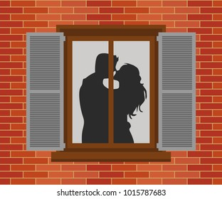Window in the house at night. Silhouettes of the guy and the girl who kiss. Valentine's Day Celebration.