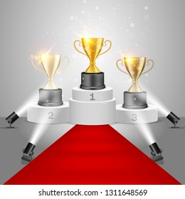 Winner awards on victory pedestal, vector realistic illustration. Gold, silver and bronze trophy cups on white podium with red carpet illuminated by floor spotlights.