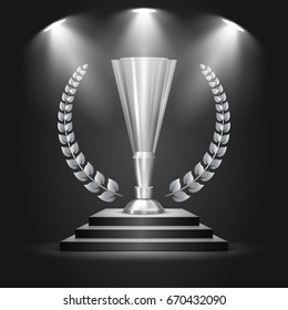 Winner silver cup with laurel wreath. Metallic trophy cup on the podium, illuminated by spotlights. Vector illustration.