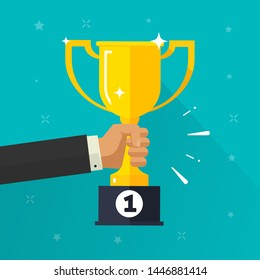 Winner success golden cup in hand vector illustration, flat cartoon award prize or achievement, competition win or best champion