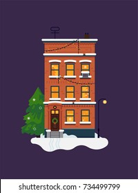 Winter holidays themed design element, vector. Flat design city red brick townhouse building in winter setting. Covered in snow residential building facade with lit up windows and christmas tree