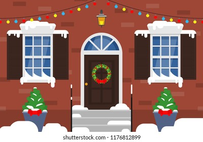 winter snowy house facade with christmas wreath on the front door