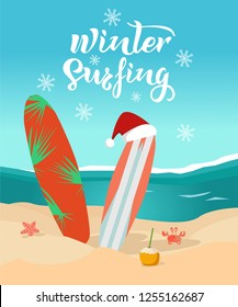 Winter surfing hand drawn inspirational text with snowflakes. Sunny day on the beach, surfboards with christmas cap, waves on the sea, crab, seastar, coconut drink. Vector illustration