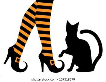 witches feet in striped socks and shoes and a black cat