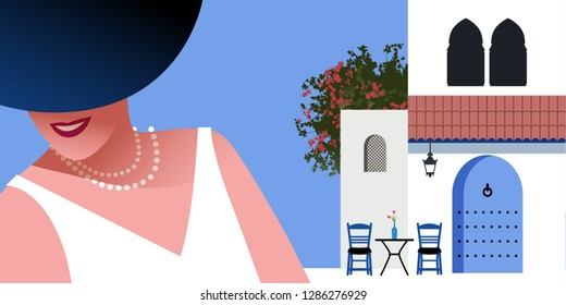 Woman with blue hat and pearls necklace, on background of typical morocco style mediterranean village. Blue door under a roof, Moorish windows, chairs and a small table with vase. Bougainvillea