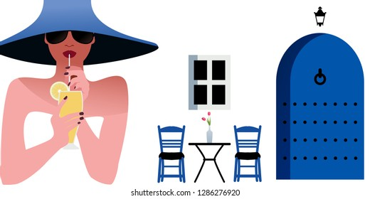 Woman with blue hat and sunglasses, drinking a lemon drink on background of typical mediterranean village. Blue door, window, chairs and table with vase on white wall.