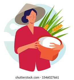 Woman farmer holding basket wearing cap in rice padi field harvesting. Traditional farming organic nature