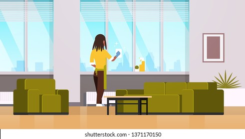woman in gloves and apron cleaning windows with rag cleaner spray rear view african american housewife doing housework concept modern living room interior horizontal flat full length