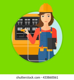 A woman in helmet measuring the voltage output. Young electrician with electrical equipment standing in front of switchboard. Vector flat design illustration in the circle isolated on background.