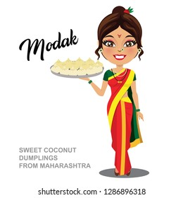 A woman from the Indian state of  Maharashra (Maharashtrian) is holding a plate of 'modak' which is a sweet cocunut dumpling famous in marathi households. She is wearing a nine yard or 'nauvari' saree