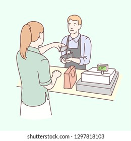 Woman paying with smartphone and male cashier holding wireless payment terminal at shop checkout counter. Buyer making mobile phone contactless payment. NFC technology. Flat line vector illustration