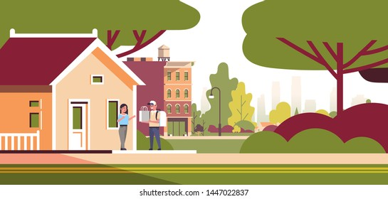 woman receiving order from man courier in cap with backpack and paper package express food delivery from shop or restaurant concept modern house building exterior flat horizontal full length