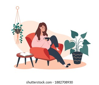 Woman sitting and resting on an armchair with coffee, rest at home