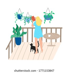 Woman standing on balcony with cat and watering hanging flowers in pots
