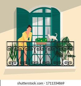 A woman stands on a balcony against a panoramic door with shutters, and a cat walks along the railing.